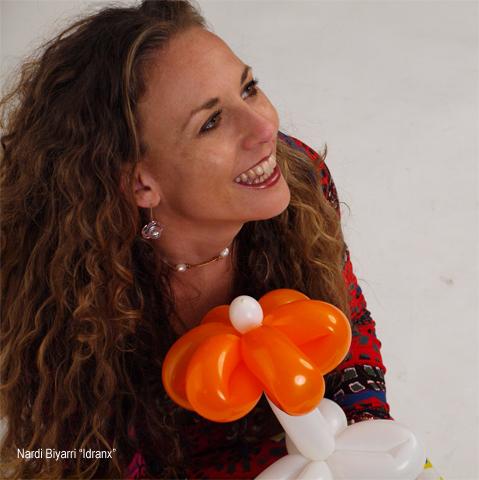 Una imagen de mi sonriendo con una flor hecha con un globo de bonitos y grandes pétalos narajas y tallo blanco