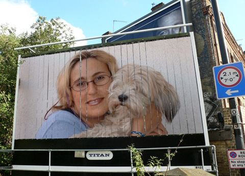 Gloria mujer de pelo rubio rizado y gafas de pasta negras y blancas que sostiene a su perra de pelo blanco entre sus dos manos
