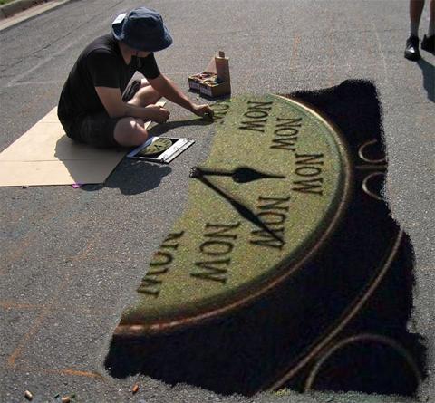 Un artista de calle está pintando en el suelo de la calle, en el asfalto, está pintando un reloj dónde todas sus horas indican NOW... AHORA