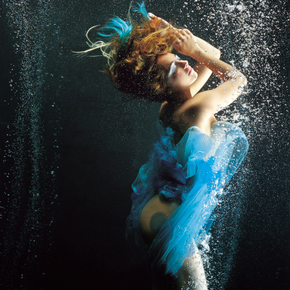 Imagen de mujer bajo el agua, tapada por velos de colores azulados mirando hacia arriba con las manos unidas en su frente