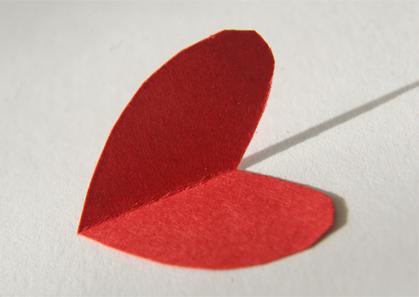 Un corazón rojo de papel doblado por la mitad encima de un fondo blanco