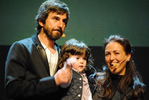 Encima del escenario del teatro Sagarra Santi Millán, Nacho y Eva Giménez, la madre de Nacho que lo lleva en brazos, y Santi coge la mano de Nacho para decir HOLA