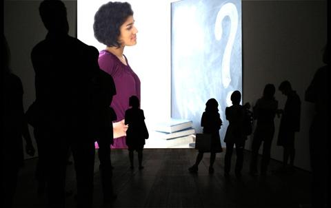 Una mujer está mirando una pizarra en la que hay un gran interrogante dibujado en tiza. A su alrededor personas que la observan como ella mira su interrogante