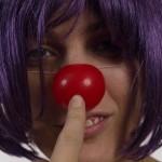 Primer plano de Hedy Kramer con una peluca lila de pelo corto y nariz roja de payaso