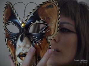 Hedy Kramer mirando una máscara veneciana con el movimiento de ir a ponérsela