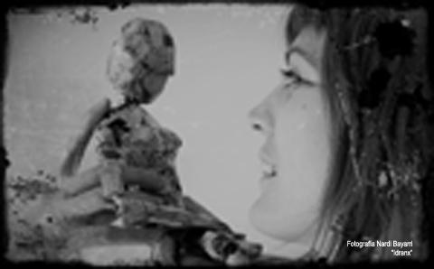 Hedy Kramer mirando de frente a una muñeca mujer hecha de papel