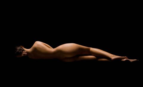 Una mujer que nos enseña su torso desnudo, estirada encima del suelo, con un fondo negro