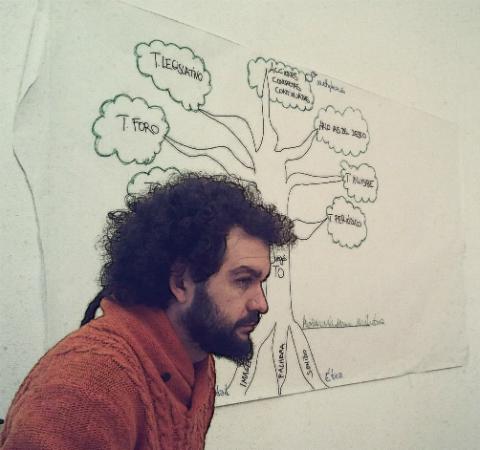 Antonio Masegosa sentado, detrás tiene la imagen del Árbol del Teatro del Oprimido