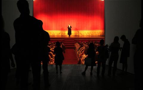 Encima de un escenario de teatro el Jocker introduce la obra que el público va a presenciar