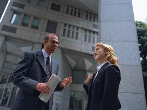 Un hombre y una mujer, vestidos con ropa formal de empresarios están hablando. El hombre tiene ahora la palabra