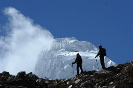 Fotografía en la que se ven dos personas equipados de montaña, y al fondo un pico de las montañas del Everest