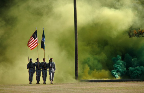 Tres hombres militares surgen entre una immensa polvareda con dos banderas izadas