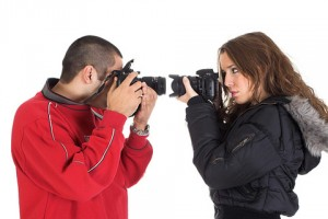 Un chico y una chica ambos con cámara en mano, dirigen sus objetivos uno hacia el otro, llevando el objetivo al rostro de cada uno respectivamente